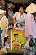 Cholon (Chinatown). Binh Tay Market. Woman selling roasted meat. Ad for Pho (noodle soup).