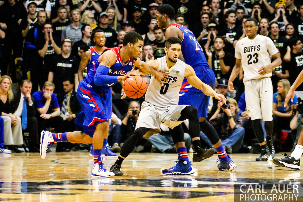December 7th, 2013:  Kansas Jayhawks freshman guard Frank Mason (0) looks for a opening past the defense of Colorado Buffaloes junior guard Askia Booker (0) in the second half of action in the NCAA Basketball game between the Kansas Jayhawks and the University of Colorado Buffaloes at the Coors Events Center in Boulder, Colorado