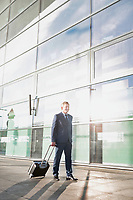 Businessman walking with his suitcase in the airport
