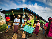 """25 OCTOBER 2015 - INSEIN, MYANMAR:  Shoppers at Danyin Market (also known as Da Nyin) in Insein, Myanmar, about 90 minutes from Yangon. Vendors in the market sell just about everything people in the area need, but mostly it's a """"wet market"""" with fruits, vegetables and meats. Most people in Myanmar still do not have refrigerators in their homes, so people go to market almost every day.    PHOTO BY JACK KURTZ"""