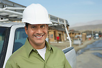 Smiling Construction Worker in hard hat standing next to truck on construction Site