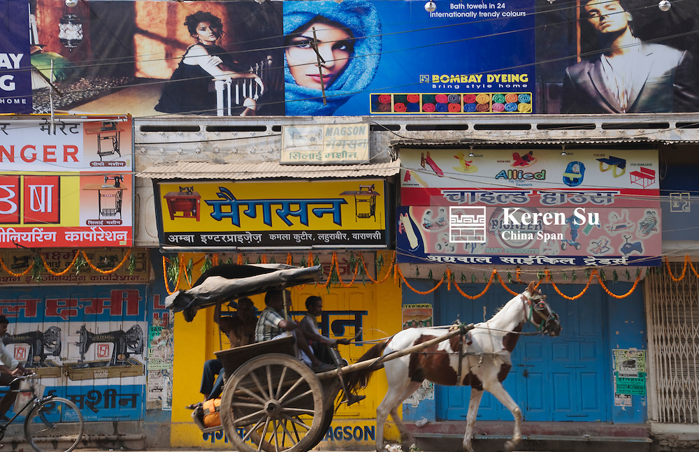 Horse cart passes by posters on the street, Varanasi, India