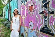 Vodou priestess Sallie Ann Glassman outside her voodoo temple in New Orleans.  The fence is the site for an annual Day of the Dead ritual.