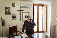 "SUTERA, ITALY - 8 JANUARY 2018: Mayor of Sutera Giuseppe Grizzanti (63) is seen here at work in his office in the town hall of Sutera, Italy, on January 8th 2018.<br /> <br /> Sutera is an ancient town plastered onto the side of an enormous monolithic rock, topped with a convent, in the middle of the western half of Sicily, about 90 minutes by car south of the Sicilian capital Palermo<br /> Its population fell from 5,000 in 1970 to 1,500 today. In the past 3 years its population has surged  after the local mayor agreed to take in some of the thousands of migrants that have made the dangerous journey from Africa to the Sicily.<br /> <br /> ""Sutera was disappearing,"" says mayor Giuseppe Grizzanti. ""Italians, bound for Germany or England, packed up and left their homes empty. The deaths of inhabitants greatly outnumbered births. Now, thanks to the refugees, we have a chance to revive the city.""<br />  Through an Italian state-funded project called SPRAR (Protection System for Refugees and Asylum Seekers), which in turn is co-funded by the European Union's Fund for the Integration of non-EU Immigrants, Sutera was given financial and resettlement assistance that was co-ordinated by a local non-profit organization called Girasoli (Sunflowers). Girasoli organizes everything from housing and medical care to Italian lessons and psychological counselling for the new settlers.<br /> The school appears to have been the biggest beneficiary of the refugees' arrival, which was kept open thanks to the migrants.<br /> Nunzio Vittarello, the coordinator of the E.U. project working for the NGO ""I Girasoli"" says that there are 50 families in Sutera at the moment."