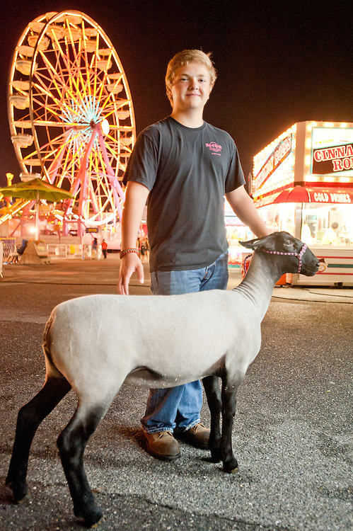 Young boy with a sheep and amusement park rides at the Maryland State Fair, Timonium MD