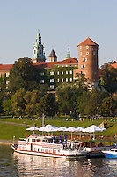 late afternoon sunlight falls on pleasure boats and the wawel castle in krakow poland.rich green, river banks with locals, plus sigismund tower can be seen.