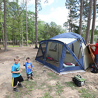 Matt Little, 5, left, and Caleb Coe, 3, play around the campground as David Coe removes the cover from his tent after the high winds stopped blowing while they stay at Chewalla Lake in Holly Springs.