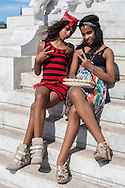 Two teenagers girl pose for a photo on a marble memorial in the centre of Havana, Cuba.