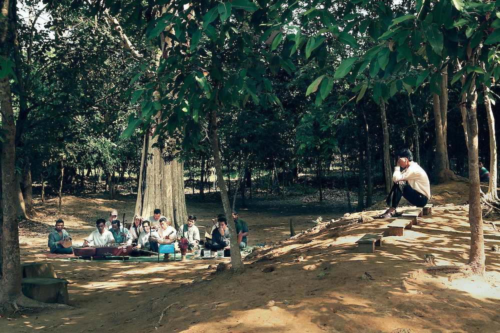 Angkor, Banteay Srei:  land mine victims' orchestra of stringed and percussion instruments plays for tourists and sells CDs of their performances.  The man with his hand to his mouth is playing a leaf as though it were a reed or flute. Man listening is seated on nearby bench.