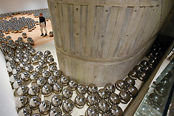 """© Licensed to London News Pictures. 25/09/2018. LONDON, UK. A gallery staff member views """"Narcissus Garden"""", 1966-, by Yayoi Kusama. Preview of """"Space Shifters"""" at the Hayward Gallery, an exhibition which features artworks by 20 leading international artists that disrupt the visitor's sense of space and alter their perception of their surroundings.  The show runs 26 September to 6 January 2019.  Photo credit: Stephen Chung/LNP"""