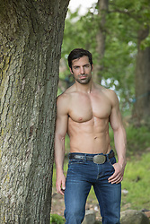 muscular shirtless man leaning against a tree in the woods
