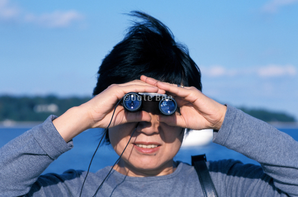 an Asian woman looking through binoculars