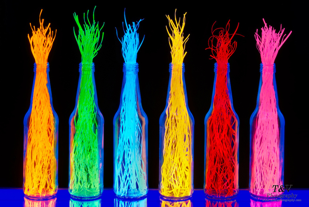 Bottles filled with shredded colorful paper.Black light