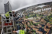 Installing a regeneration project hoarding image at Elephant & Castle, London borough of Southwark.