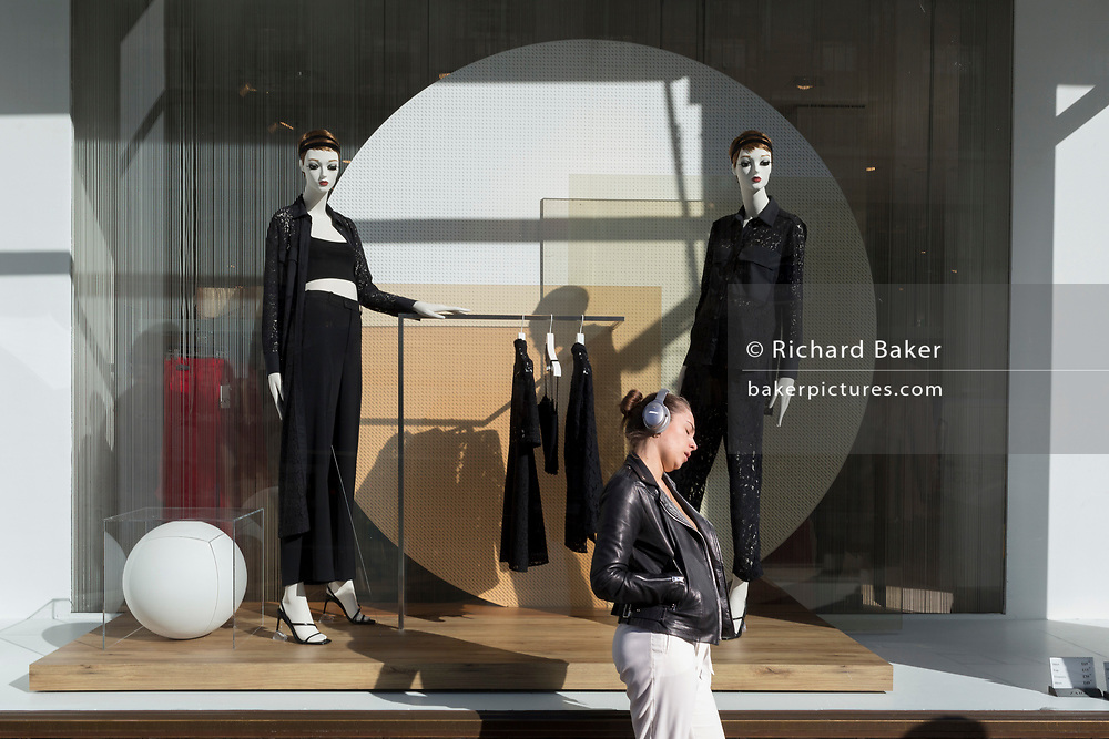 A young woman rests her head against the window beneath retail mannequins on Regent Street in Westminster, on 26th February, in London, England.