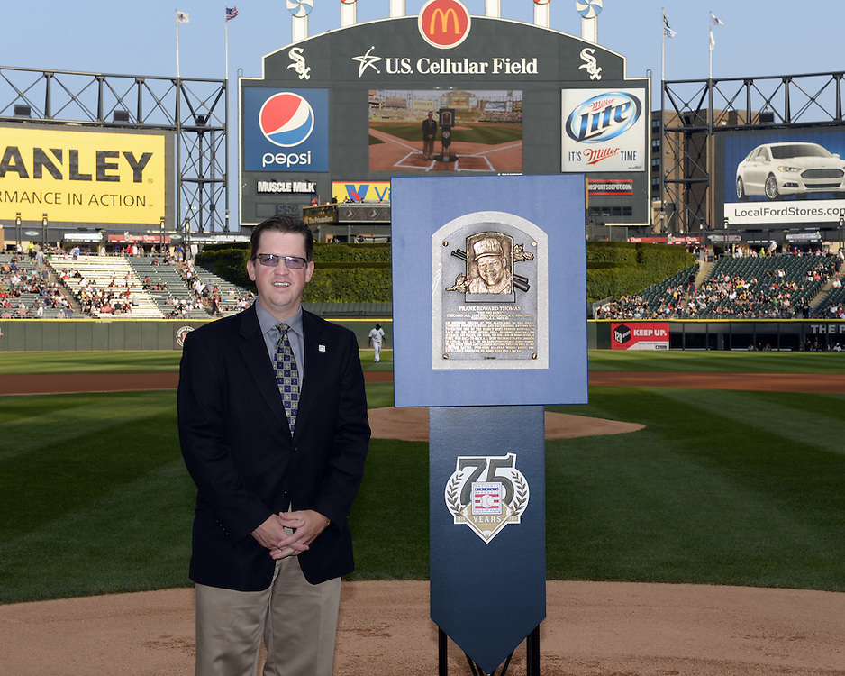 """CHICAGO - AUGUST 2:  Baseball Hall of Fame official Brad Horn poses next to the official plaque of 2014 Baseball Hall of Fame Inductee Frank Thomas at U.S. Cellular Field during a special """"trip"""" that the plaque took over the weekend of August 2-3, 2014."""