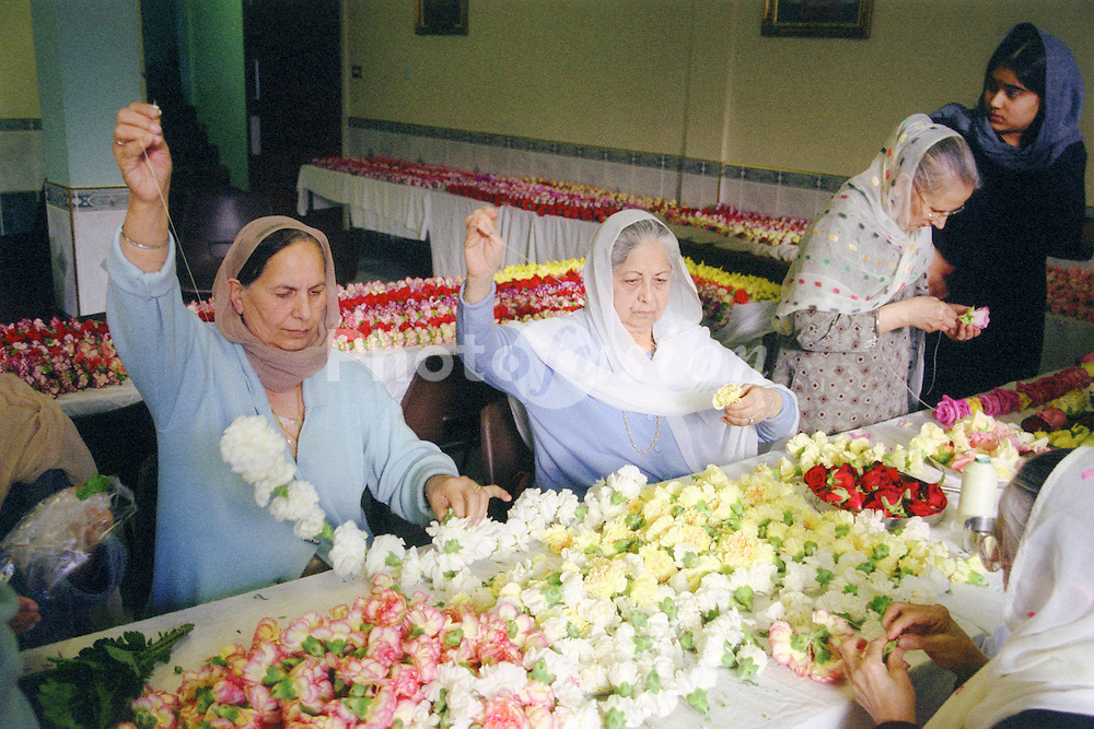 Elderly Asian women making garlands for the Baisakhi festival,