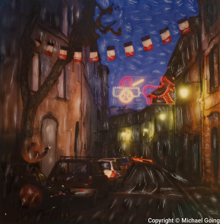Christmas decorations in ancient and medieval Village d Bargeme of Santa Claus with lighted sled, reindeer and French flags, hanging across narrow street  at night