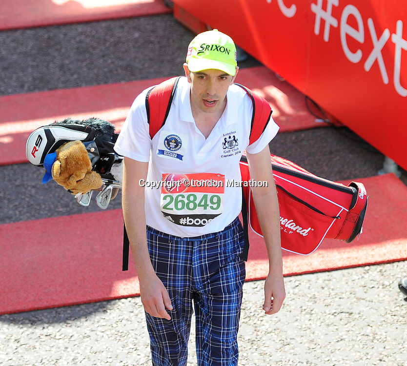 A runner completes the race with a set of golf clubs on his back<br /> The Virgin Money London Marathon 2014<br /> 13 April 2014<br /> Photo: Javier Garcia/Virgin Money London Marathon<br /> media@london-marathon.co.uk