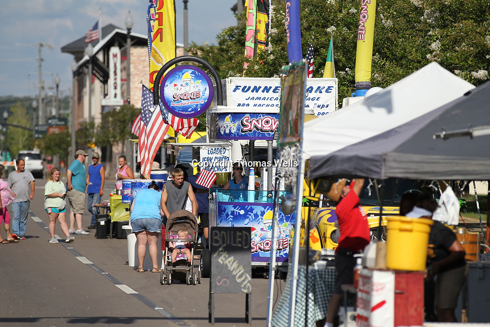 Residetns make their way down the Main Street and check out the food vendors during Tuesday's All Amercia Picnic in Tupelo at Fairpark.