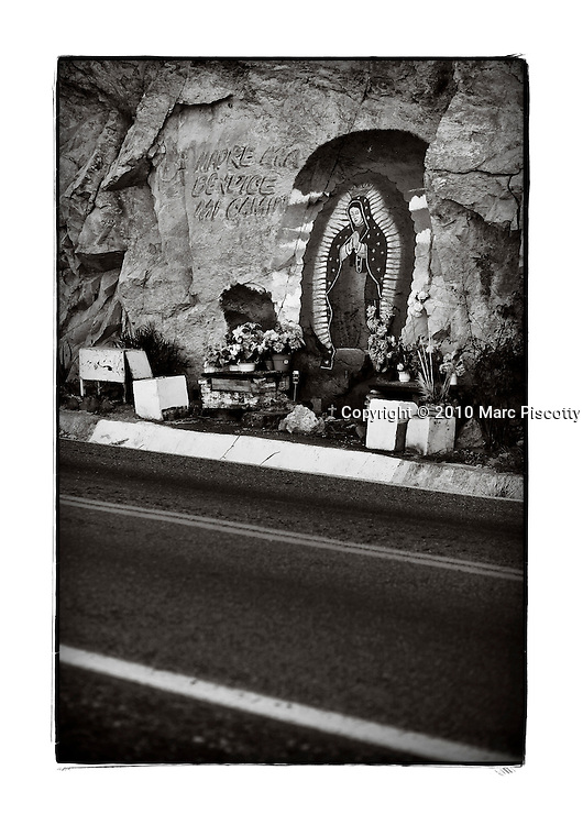 "SHOT 1/30/10 5:14:08 PM - The Virgin Mary painted on rock along Highway 15 near Coyotitian, Mexico. The Virgin of Guadalupe has symbolized the Mexican nation since Mexico's War of Independence. Our Lady of Guadalupe (Spanish: Nuestra Señora de Guadalupe) is a celebrated Catholic icon of the Virgin Mary also known as the Virgin of Guadalupe (Spanish: Virgen de Guadalupe). The Lady of Guadalupe is of significant importance to Mexican Catholics and has been given the titles of ""Queen of Mexico"", ""Empress of the Americas"", and ""Patroness of the Americas"". Roadside capillas, or tiny chapels, in the Mexican states of Nayarit, Sinaloa and Sonora. The capillas are common along the roads and highways of Mexico which is heavily Catholic and are often dedicated to certain patron saints or to the memory of a loved one that has passed away. Often times they contain prayer candles, pictures, personal artifacts or notes. (Photo by Marc Piscotty / © 2010)"