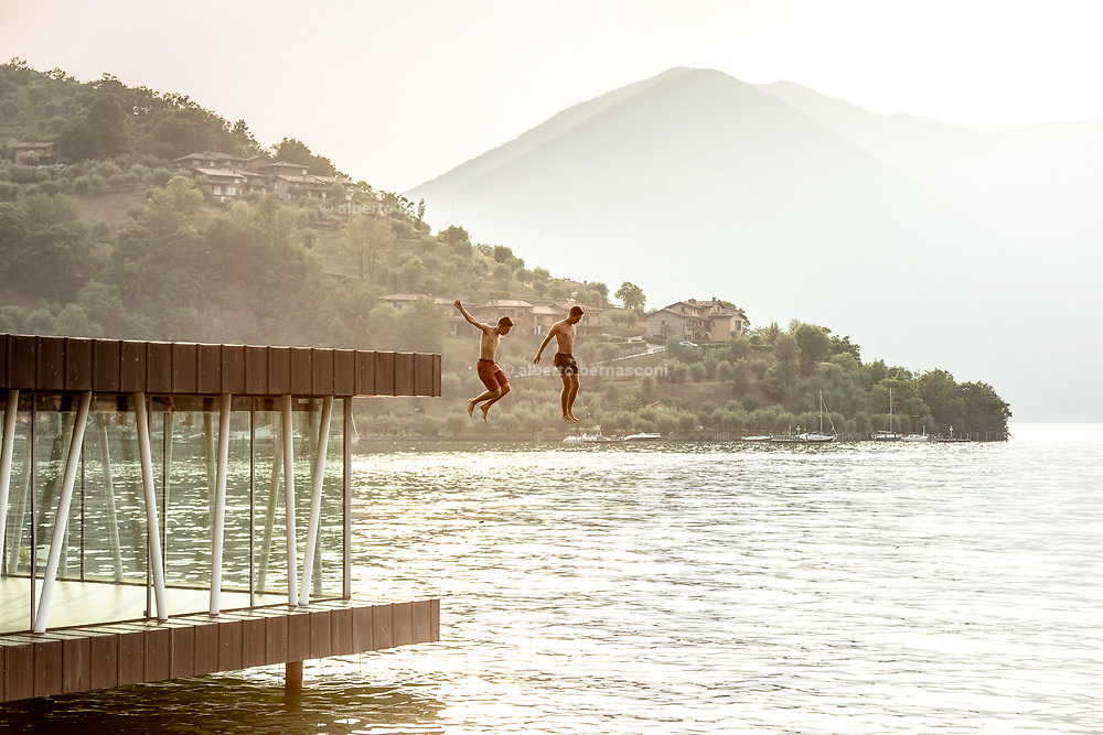 iTALY, ISEO LAKE, guys jumping from an abandoned building along the lake near Pilzone
