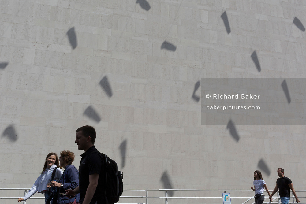 Visitors to the Southbank walk beneath the shadows of tube kites cast on an exterior concrete wall of the Royal Festival Hall on the Southbank, on 15th August, in London, England.