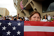 Isabel Salinas from San Luis Potosi in Mexico holds an American flag to partially cover her face in front of Dallas City Hall  during the MegaMarch for Immigration Reform, May 01, 2010