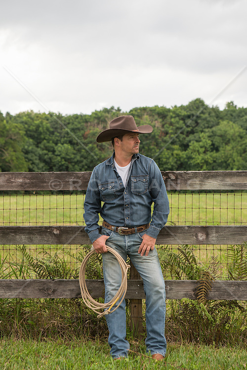 good looking cowboy on a ranch leaning against a fence