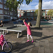 Nederland Rotterdam 01-10-2009 20091001 Foto: David Rozing     Achterstandswijk Crooswijk, twee meiden spelen buiten op straat. Ze pasen de roze bal via de tafeltennistafel over en weer naar elkaar, samenspelen.  Two girls playing in Crooswijk, deprived area in Rotterdam, nieghbourhood.                                                           .Foto: David Rozing
