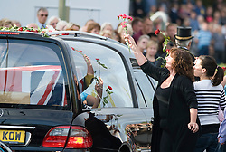 © licensed to London News Pictures. 08/09/2011. Brize Norton, UK..Members of the public throw red flowers on to the hearse carrying the body of  of Sergeant Barry Weston of 42 Commando Royal Marines as it passes through Carterton after arriving at RAF Brize Norton for the first time. Sgt Weston was killed on August 30 while leading a patrol near the village of Sukmanda in southern Nahr-e Saraj, Helmand province. Photo credit: Ben Cawthra/LNP