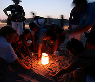 A family leaves hand prints in the sand around a candle during a vigil marking the 10th anniversary of the TWA Flight 800 disaster at Smith Point Park in Shirley, New York, Monday 17 July 2006