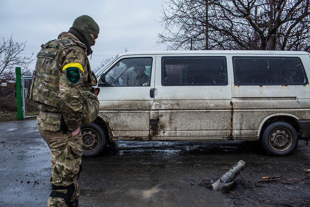 TALAKIVKA, UKRAINE - FEBRUARY 5, 2015: Members of the St. Mary's Battalion, a pro-Ukraine militia, examine the remains of a grad rocket that landed in the middle of the road in Talakivka, Ukraine. With more than 220 people having died in the past several weeks, a new diplomatic push is underway to bring an end to fighting between pro-Russia rebels and Ukrainian forces. CREDIT: Brendan Hoffman for The New York Times