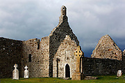 Low angle view of Clonmacnoise Cathedral, 909, from the south-east (centre and left), Temple Doolin or Dowling, 10th century, restored 1689, and Temple Hurpan, 17th century,  (right), Clonmacnoise, County Offaly, Ireland, in the evening. Clonmacnoise was founded by St Ciaran, with the help of Diarmait Ui Cerbaill, Ireland's first Christian King. The site presents the largest collection of Early Christian graveslabs in Western Europe. Picture by Manuel Cohen