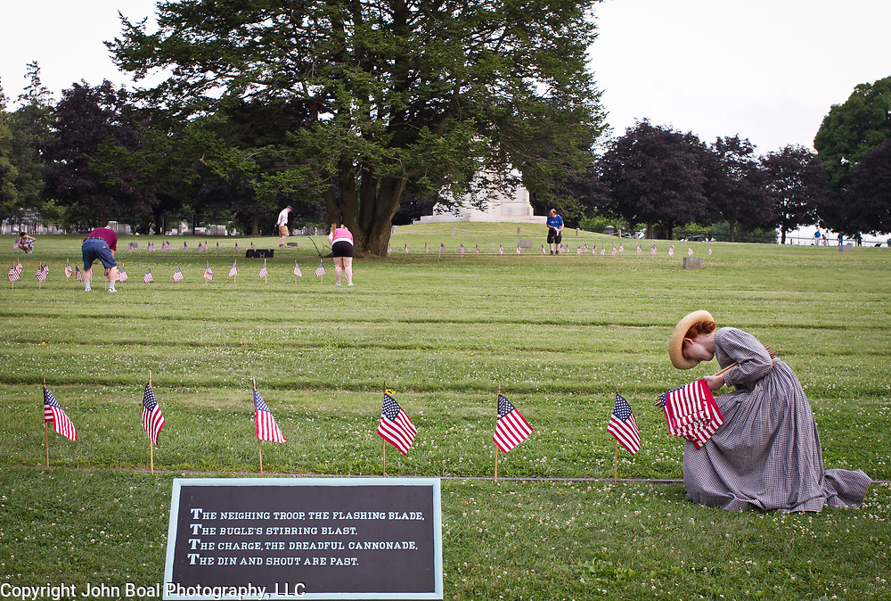 Judy Neemeyer, 14, plants flags at Soldiers National Cemetery, during the Sesquicentennial Anniversary of the Battle of Gettysburg, Pennsylvania on Sunday, June 30, 2013.  A pivotal battle in the Civil War, over 50,000 soldiers died in the battle which spanned 3 days from July 1-3, 1863.  Later that year, President Abraham Lincoln returned to Gettysburg to deliver his now famous Gettysburg Address to dedicate the cemetery there for the Union soldiers who died in battle.  John Boal photography