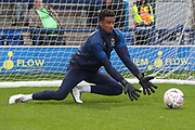 AFC Wimbledon goalkeeper Nathan Trott (1) warming up and saving a ball in the rain during the The FA Cup match between AFC Wimbledon and Doncaster Rovers at the Cherry Red Records Stadium, Kingston, England on 9 November 2019.