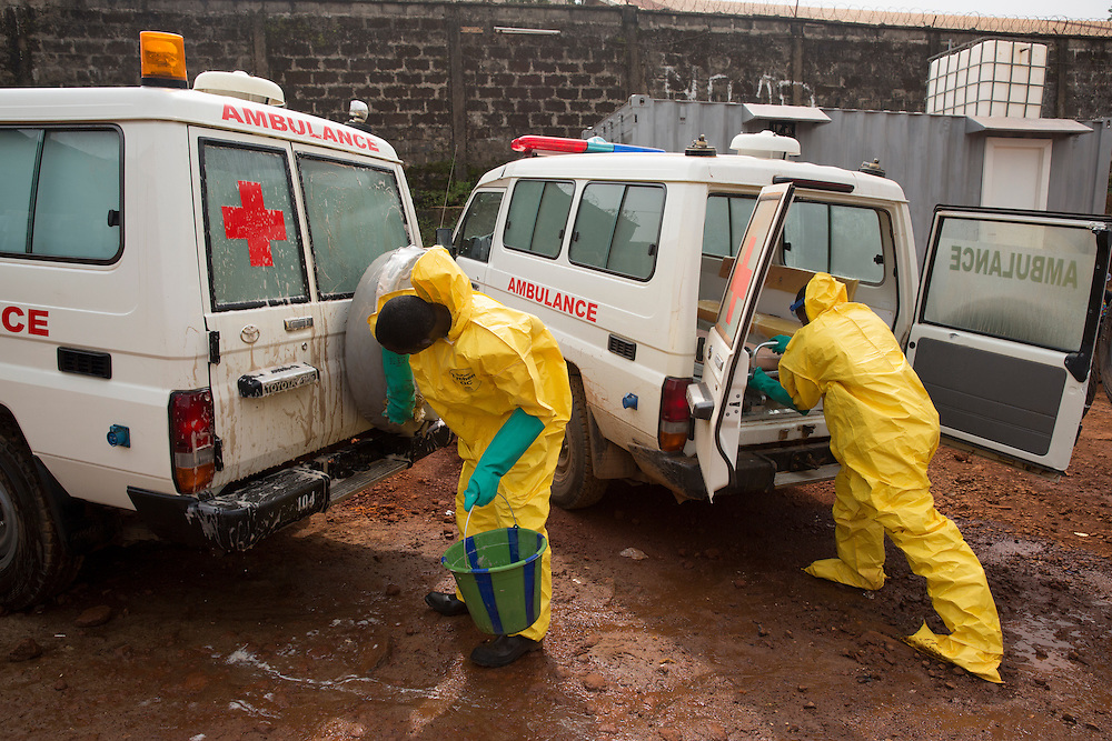 Ambulance depot from the Western Area Emergency Response Center. Once a call has been made for a suspected case, an ambulance is going to be dispatched to carry the case to the Holding  station where a test will be done. Seen here are ambulance drivers, nurses and cleaners at the depot. Cleaners have the task to completely disinfect the ambulance after it carried a susptected case with chlorine so it gets ready for the next trip. Martine Perret/UNMEER. 15 December 2014