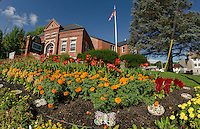 Beautiful flower gardens adorn the front lawn of the Meredith Public Library.  (Karen Bobotas/for the Laconia Daily Sun)
