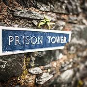 Sign for the prison tower at Harlech Castle in Harlech, Gwynedd, on the northwest coast of Wales next to the Irish Sea. The castle was built by Edward I in the closing decades of the 13th century as one of several castles designed to consolidate his conquest of Wales.