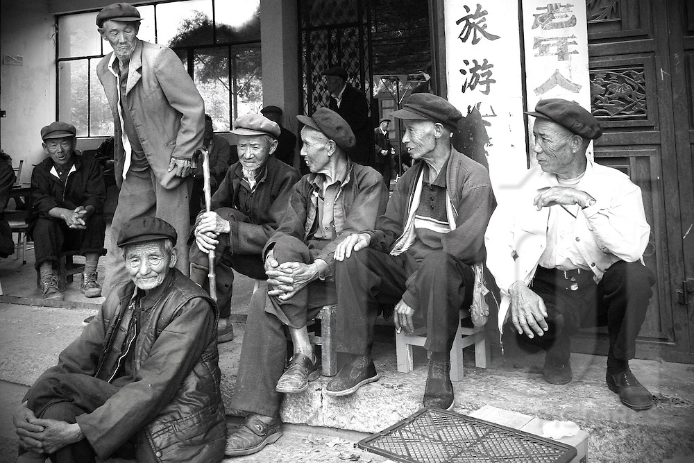 Group of old men hanging out in the street of a village close from Dali