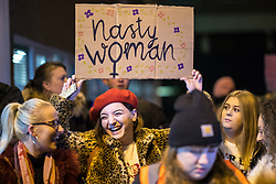 """© Licensed to London News Pictures . 22/02/2018 . Manchester , UK . A woman holds a """" Nasty Woman """" placard in the crowd . 100s of protesters , campaigning against the sexual harassment, abuse, rape and victim-blaming suffered by women, hold a Reclaim the Night march and rally from Owens Park in Fallowfield to the Manchester Academy on Oxford Road . Photo credit : Joel Goodman/LNP"""
