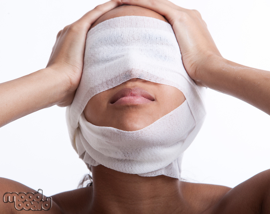 Young woman with head wrapped in bandage against white background