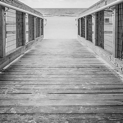 Pensacola Florida Casino Beach wooden boardwalk walkway black and white photo. Pensacola Beach is on Santa Rosa Island in the Emerald Coast region of the Southeastern United States. Photo is vertical and high resolution. Copyright ⓒ 2018 Paul Velgos with All Rights Reserved.
