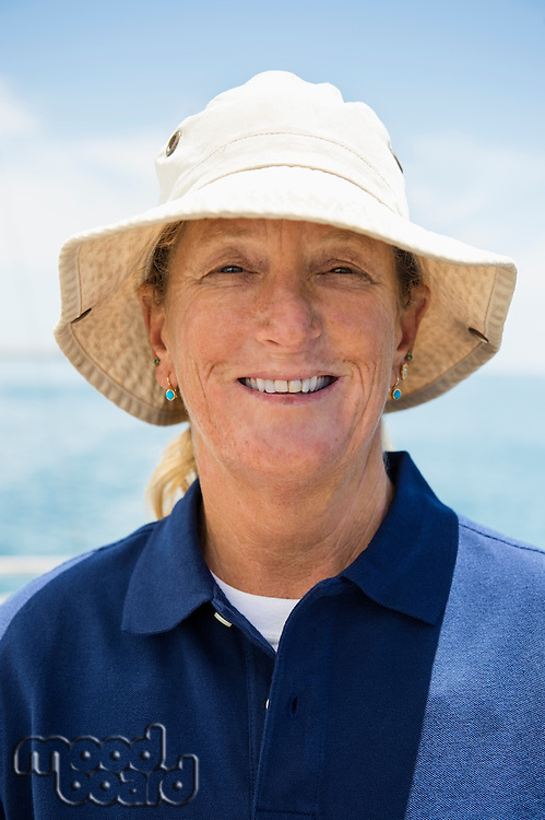 Portrait of smiling woman wearing hat on yacht