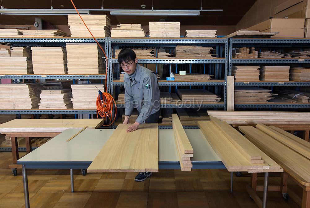 A craftsman aligns the lengths of kiri wood in preparation for laminating at  Kamo Kiri-tansu maker Asakura Kagu in Niigata City, Niigata Prefecture Japan on Feb. 21, 2017. ROB GILHOOLY PHOTO