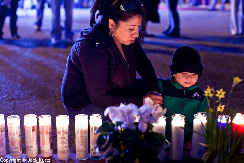 tucsonshooting - 09 JANUARY 2011 - TUCSON, AZ: Pati Castellanos (CQ) and her son, Julian Castellanos (CQ), 3, light candles at a memorial for Gabrielle Giffords at University Medical Center in Tucson Sunday night. Congresswoman Gabrielle Giffords, US Federal Judge John Roll and several other people were shot by a lone gunman in a mass shooting Saturday.     ARIZONA REPUBLIC PHOTO BY JACK KURTZ