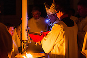 DENVER, CO - APRIL 19: Archbishop Samuel J. Aquila, left, reads from scripture held by John Brooks, right, during the Easter Vigil Mass at the Cathedral Basilica of the Immaculate Conception on April 19, 2014, in Denver, Colorado. (Photo by Daniel Petty/Denver Catholic Register)