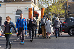 Pedestrians get about 5 seconds of time between their green light and the red at The intersection at Highbury Corner where temporary traffic lights give pedestrians, who have to wait 60 seconds, just 6 seconds of green to cross the busy A1, a major arterial road, outside the entrance to the Highbury & Islington Tube station. London, April 18 2019.