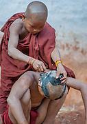 Boy buddhist monk shaving a novice's head (Myanmar)