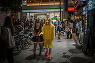 Man dressed as a chicken is walking through the streets of Shibuya on Halloween.  Tokyo, Japan.